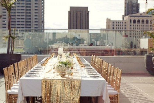 a gold glitter table runner, gold glasses and chairs create a glam look and feel at the reception