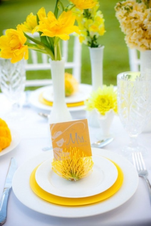 a bright spring wedding tablescape with white and yellow plates, yellow blooms in white vases and neutral cutlery is fun and cool