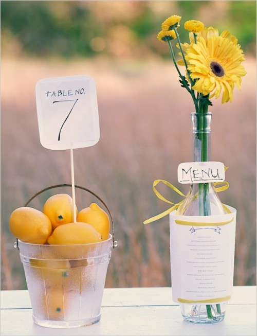 bold and simple spring wedding decor with a glass basket with lemons, a table number, a bottle with bold blooms