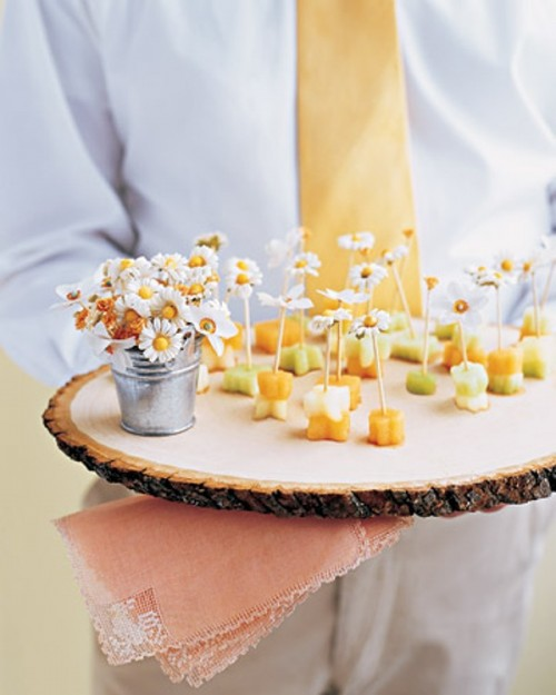 mini fruit skewers topped with fresh blooms and served on a wood slice are a lovely and cool wedding dessert