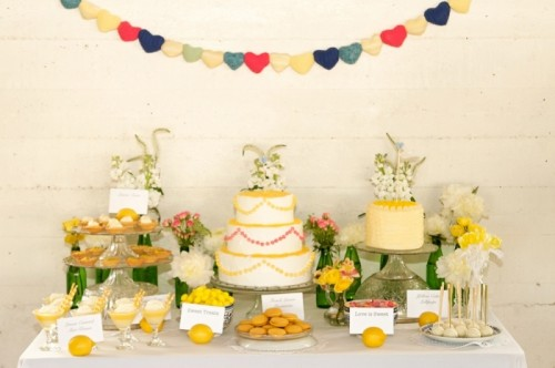a bright and fun wedding dessert table with various sweets, bold blooms and greenery and a bold banner over it