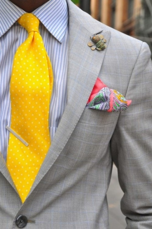 a bold and fun look with a grey plaid suit, a striped shirt and a yellow polka dot tie plus a colorful pocket square and a fun bee brooch