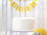a white wedding cake with a bold yellow banner as a topper and a matching banner on the wall for a bright spring wedding