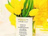 a bold wedding centerpiece of yellow tulips with a menu printed on the vase is a very cool and bold idea