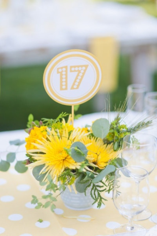 a bright wedding centerpiece with a bucket with greenery, bold yellow blooms and a printed table number