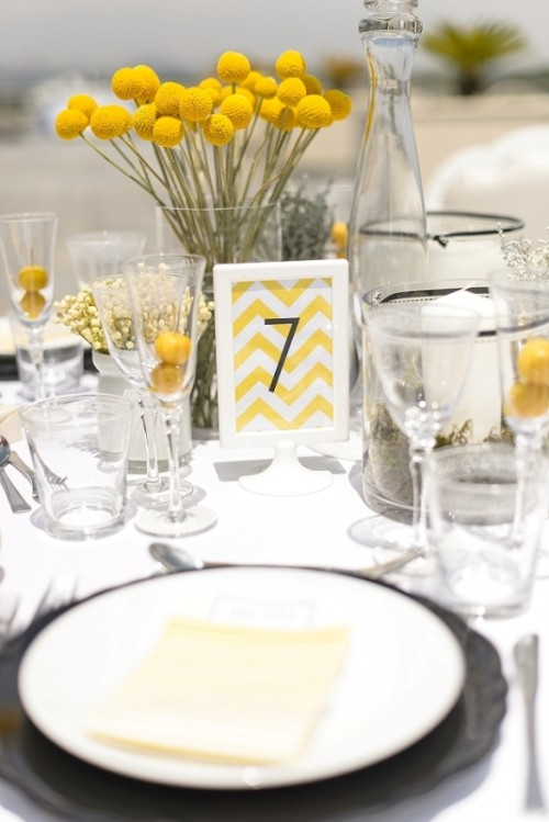a bold wedding tablescape with billy balls, a bright table number and yellow menus, neutral linens and plates
