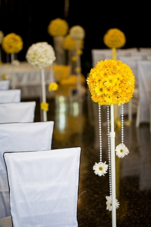 bold yellow topiaries with beads and blooms to decorate a wedding venue or an aisle