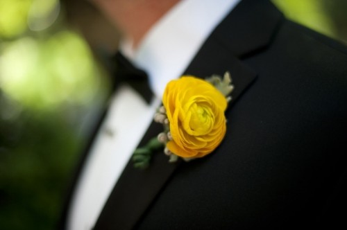 a black tux and a bold yellow boutonniere for an elegant and chic look at the wedding