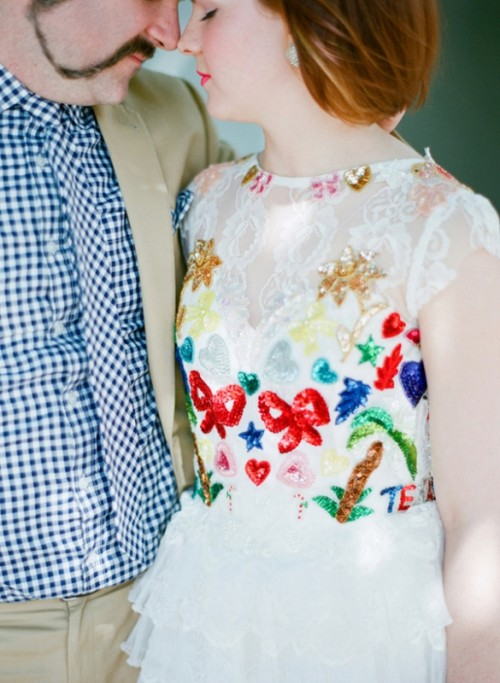 a funny detailed lace wedding dress with primitive colorful embellishments in various colors is meaningful