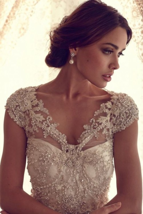 a fully embellished, embroidered and pearled wedding dress with cap sleeves strikes at once