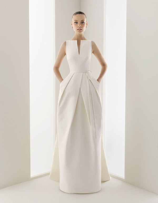 a sculptural minimalist wedding dress with a catchy pleated skirt with pockets is a very daring and bold solution