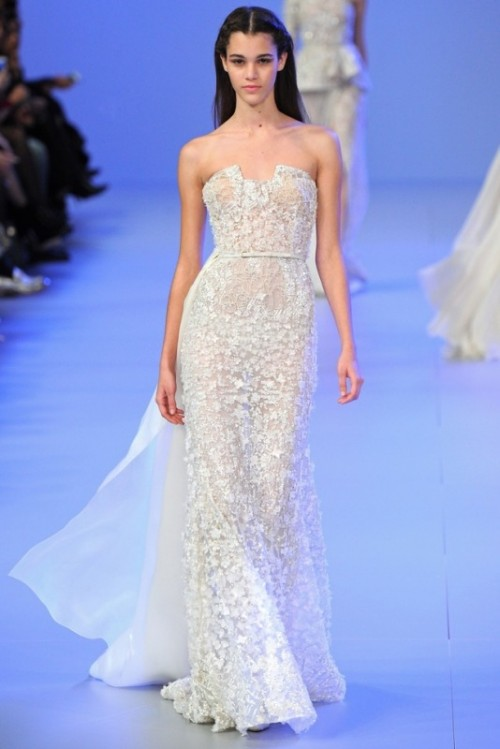a semi sheer lace embellished sheath wedding dress with a sculptural bodice and a train is a lovely and very glam idea