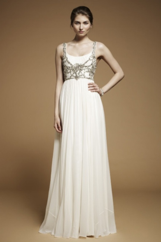 a simple neutral A line wedding dress with catchy contrasting embellishments that cover and accent the bodice of the dress