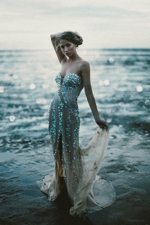 a strapless mermaid-inspired fully embellished wedding dress with a small train for a lovely beach bridal look