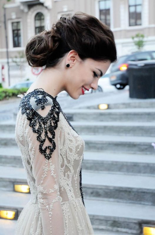 a nude lace wedding dress with heavily embellished shoulders in black that make a bold and chic statement