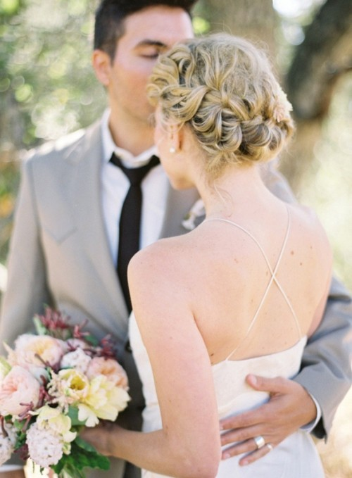 a braided updo with a messy top is an elegant and chic wedding hairstyle to try