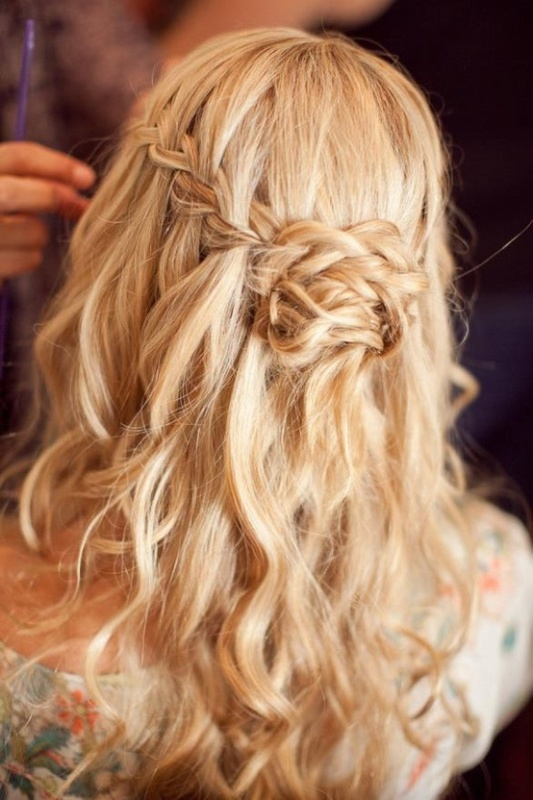 a messy wavy half updo with a braided halo and a braided knot for a relaxed and boho look