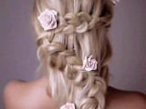 a unique half updo with several braids and fabric blooms integrated to make it more romantic