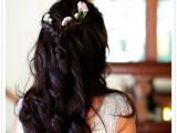 a wavy half updo with a braids plus fresh blooms that contrast dark hair