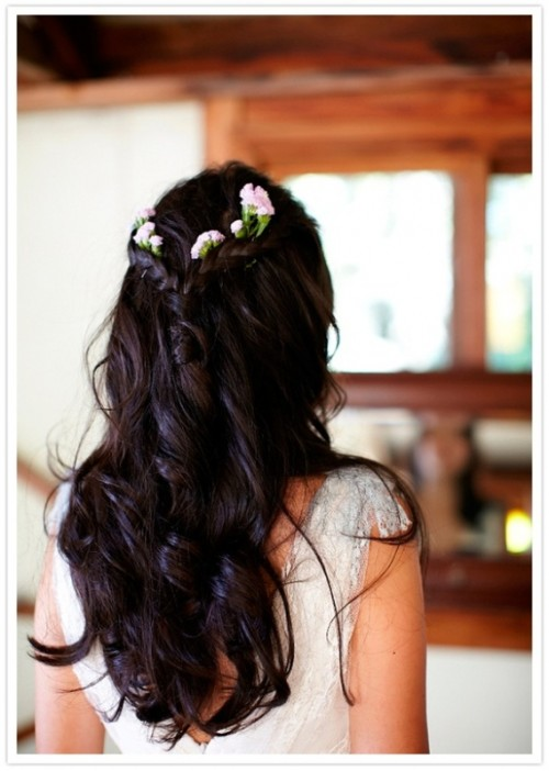 a wavy half updo with a braids plus fresh blooms that contrast dark hair