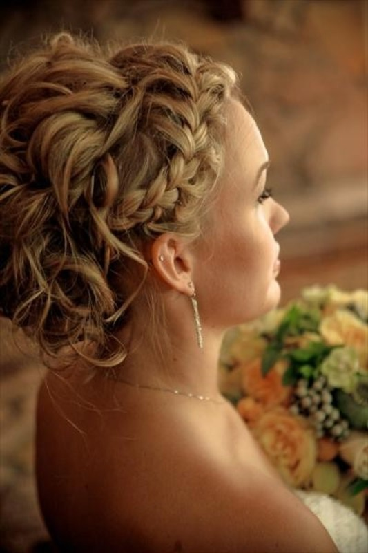 a wavy updo with a messy feel and a braided halo is a creative idea with much texture