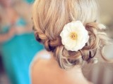 a low braided side updo with a single bloom is a chic and timeless idea that fits most of bridal styles