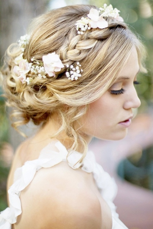 a messy updo with a braided halo plus pink roses and baby's breath for a romantic and relaxed bridal look
