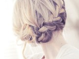 a laconic braided updo with some waves down is a durable and stylish hairstyle for a wedding
