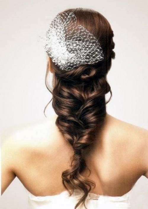 a sleek top plus a twisted and messy braid with much dimension and a veil is creative and relaxed option