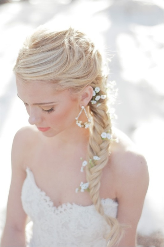 a messy fishtail braid with baby's breath tucked in for a more relaxed and boho chic look