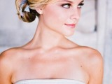 a sleek low bun with a braided halo plus a printed blue ribbon in the bun is a chic and beautiful idea