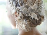 a low wavy updo with two braids and an embellished hairpiece for vintage elegance and chic