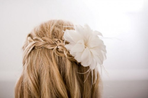 a half updo with a braid and a fresh bloom on top is a chic an simple idea suitable for both medium length and long hair