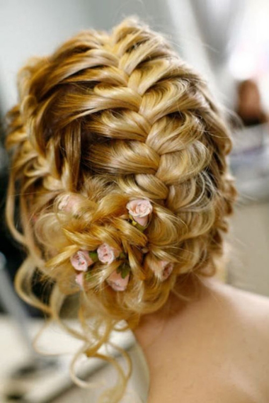 an updo that consists of several braids and is spruced up with fresh blooms