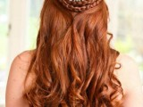 a half updo with a double braid halo, waves and an embellished hairpiece that highlights the braids