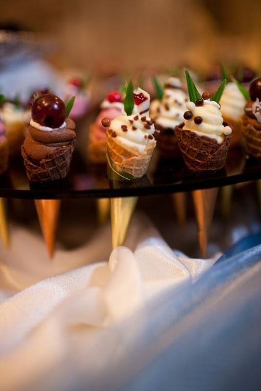 mini ice cream cones with fresh berries on top and some greenery are a timeless idea to go for