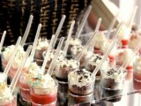 small cups with fresh berry and chocolate mousse topped with whipped cream and sprinkles