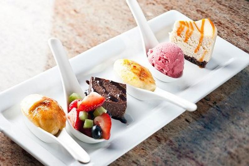 sweet mini desserts on spoons   ice cream, fruits with chocolate, cheesecakes and brownies with chocolate sauce