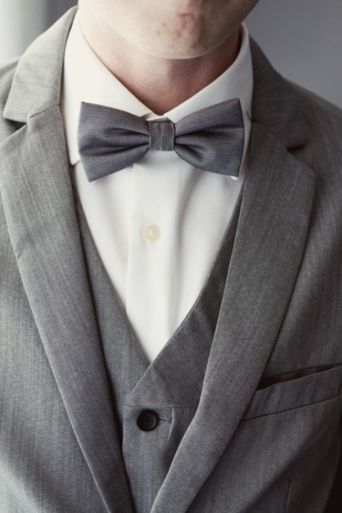 a stylish three-piece grey suit, a white shirt and a bow tie compose a timeless groom's look
