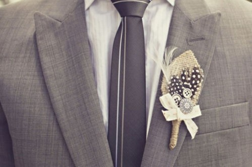 a grey suit, a white shirt, a grey striped tie and a cool feather boutonniere for a modern groom's outfit