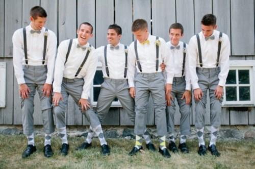 groomsmen wearing white shirts, black suspenders, grey pants, printed socks and black shoes