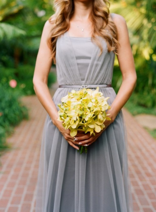 a grey sleeveless pleated maxi bridesmaid dress with a thin sash and a yellow bouquet to contrast it