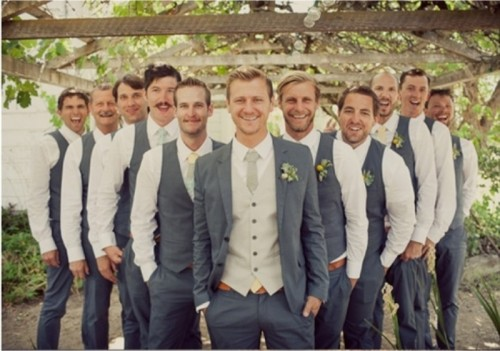a groom wearing a grey suit and a grey tie and groomsmen wearing grey pants, vests and white shirts