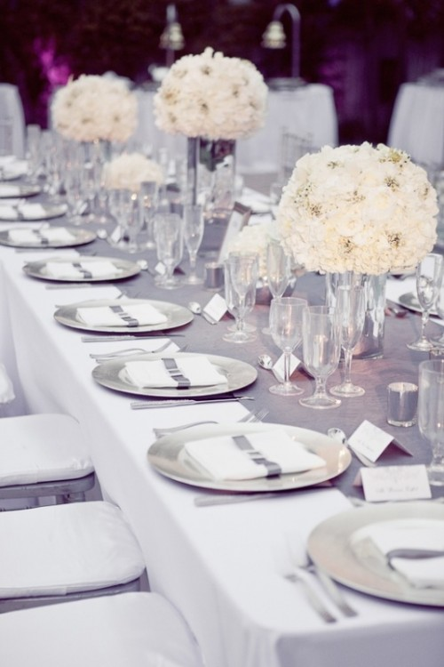 a silver grey table runner, matching plates, cards and candles paired with whites for a cool glam wedding tablescape