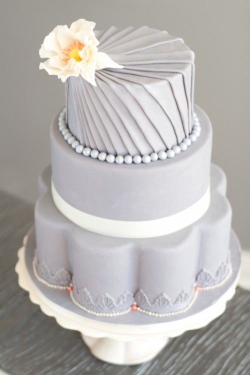 a whimsical grey wedding cake with various tiers, with beads, sugar blooms and creative shapes