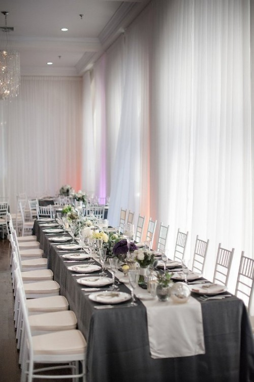 a grey tablecloth paired with white and purple blooms and greenery for a timelessly cool wedding tablescape