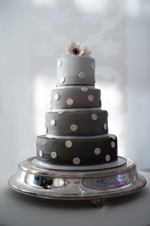 a multi-tier wedding cake in various shades of grey and with polka dots is a cool idea to rock