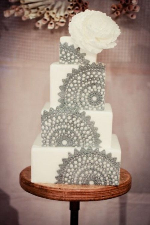 a white square wedding cake decorated with grey lace is a chic and bold dessert to try