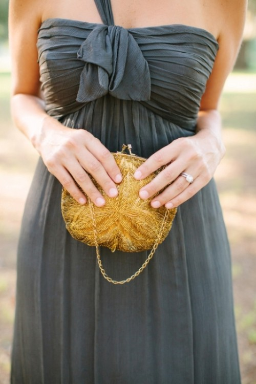 a grey one shoulder draped maxi bridesmaid dress with a gold beaded bag is a bold combo