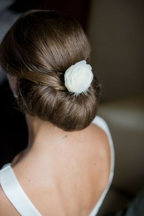 a modern twisted low updo with some sleek volume on top and a white faux bloom for a very refined and elegant look